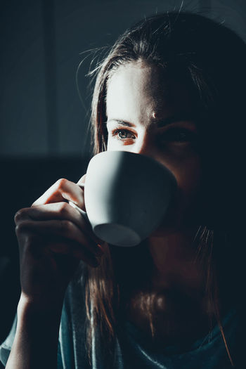 Close-Up Of Thoughtful Woman Drinking Coffee At Home