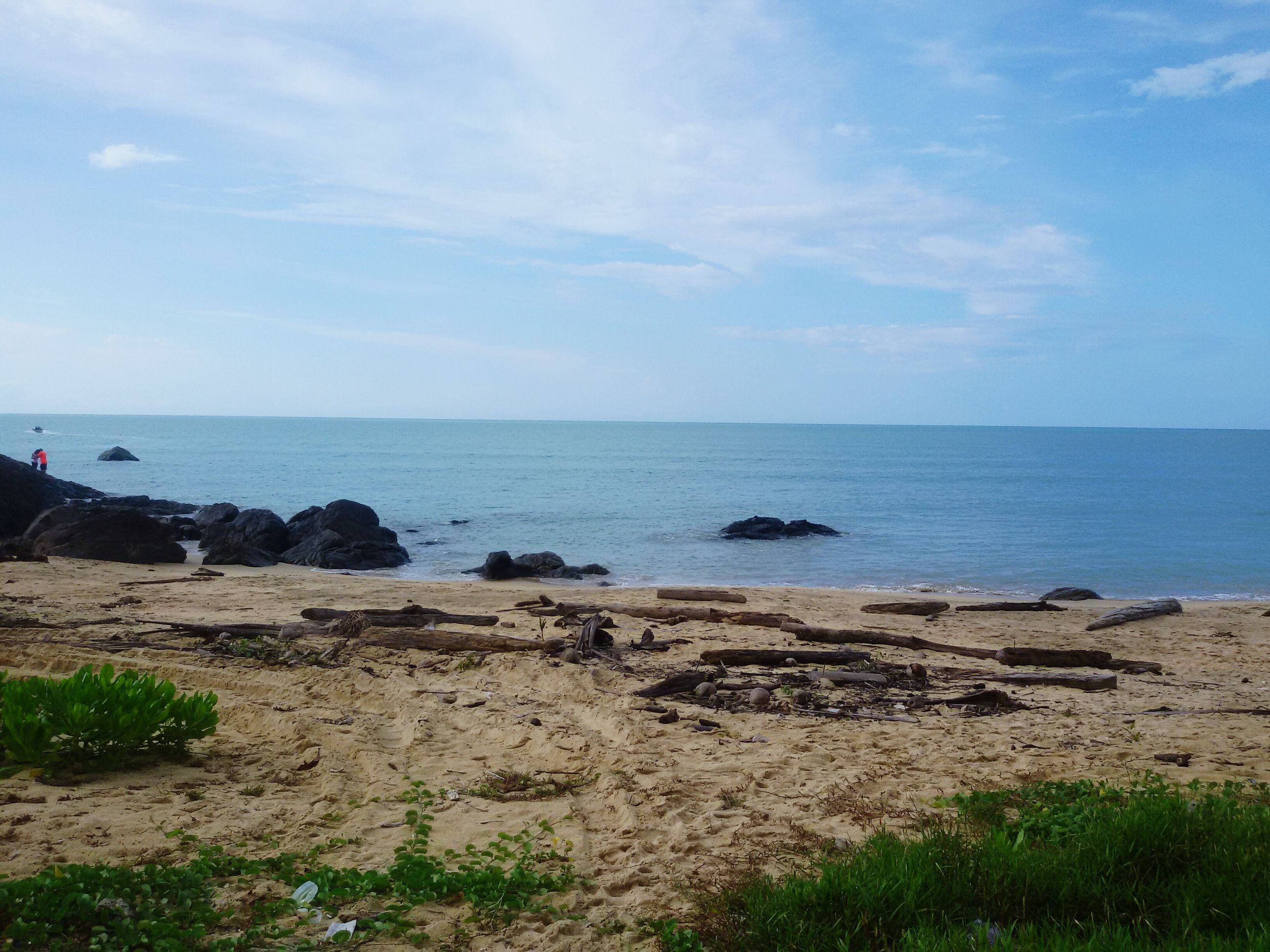 sea, horizon over water, beach, water, tranquil scene, sky, tranquility, shore, scenics, beauty in nature, nature, sand, idyllic, coastline, grass, blue, rock - object, day, remote, cloud - sky