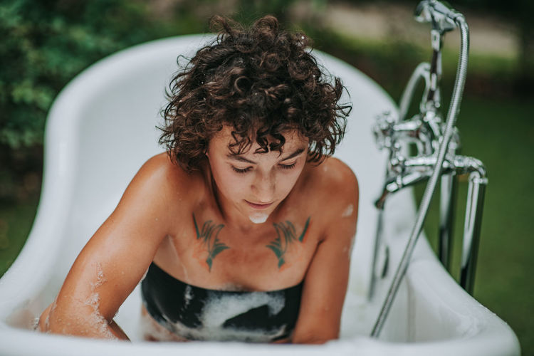 Young woman sitting in bathtub outdoors