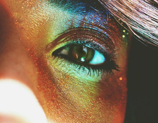 Cropped portrait of woman eye with colorful make-up