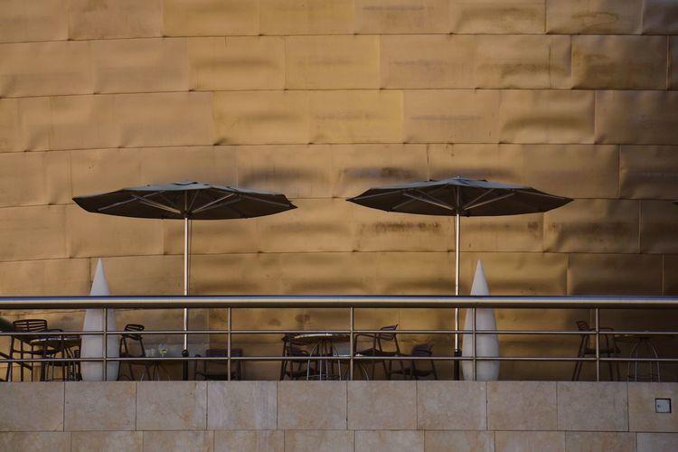 Umbrella on sidewalk against building