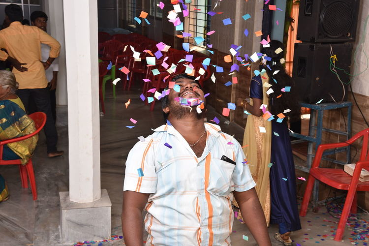 Smiling Man Standing Amidst Confetti At Home