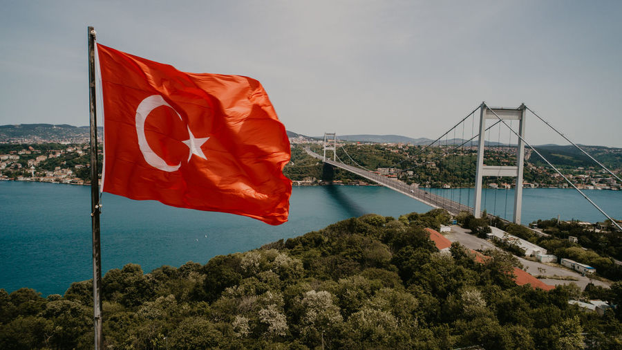 Red flag on bridge over sea against sky
