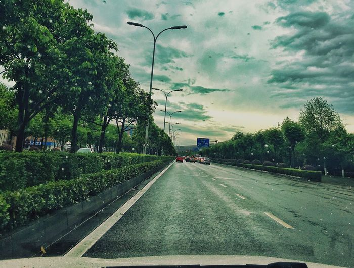 Bad weather on the road while driving Tree Road Transportation Sky Street Car Cloud - Sky The Way Forward No People Street Light Mode Of Transport Day Outdoors Land Vehicle Built Structure Green Color City Nature Architecture