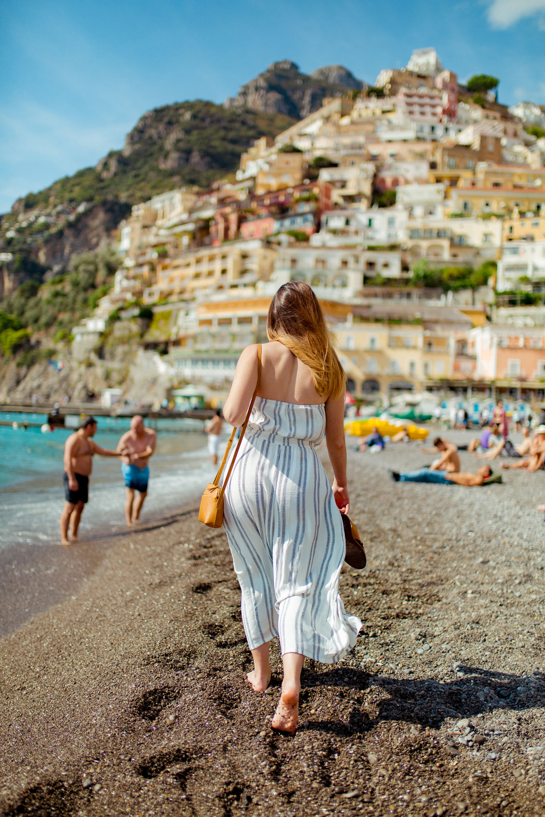 full length, real people, rear view, architecture, leisure activity, women, beach, nature, lifestyles, land, built structure, walking, focus on foreground, day, adult, casual clothing, mountain, water, building exterior, people, outdoors, hairstyle