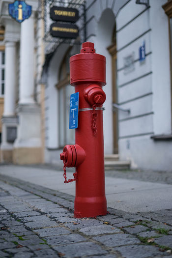 Red fire hydrant on footpath by building