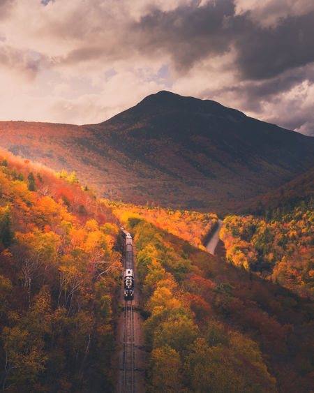Scenic view of scenic railroad and mountains against sky during autumn