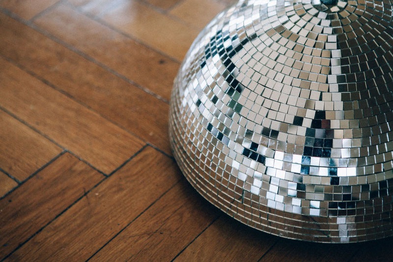 High angle view of shining disco decoration on hardwood floor