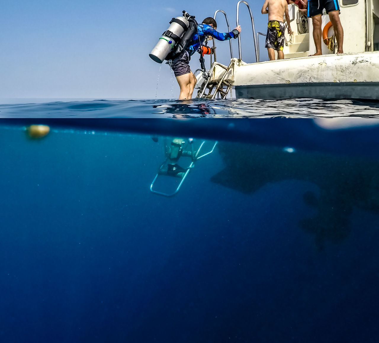Man climbing ladder on boat during scuba diving