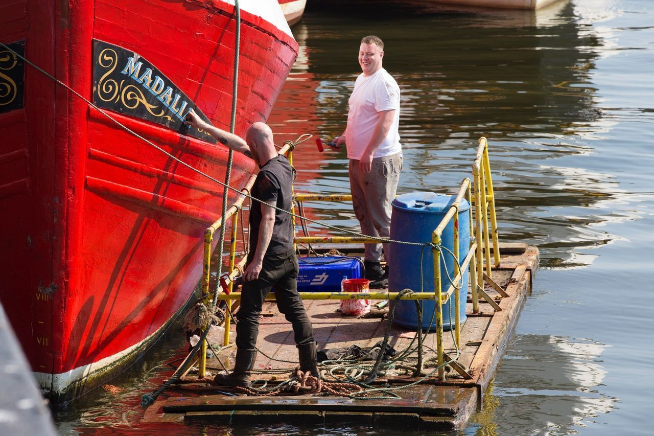 nautical vessel, mode of transportation, transportation, water, men, real people, casual clothing, people, day, standing, occupation, two people, rear view, nature, full length, outdoors, young adult, working, fisherman