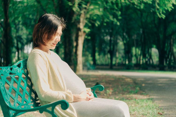 Pregnant woman sitting outdoors