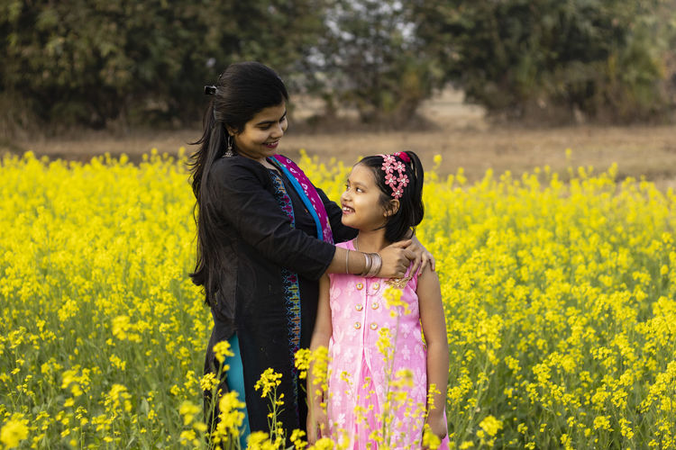 A pretty indian mother and daughter looking at each other and standing in mustard flower field