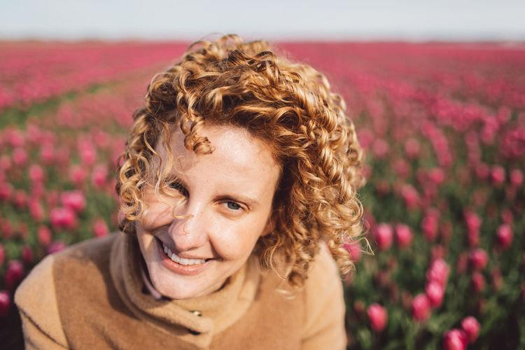 Portrait of woman in a pink tulip field