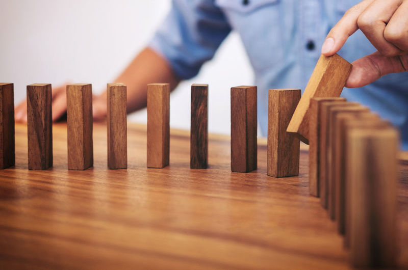 Midsection Of Man Arranging Wooden Blocks On Table