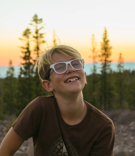 Portrait of boy wearing sunglasses against sky