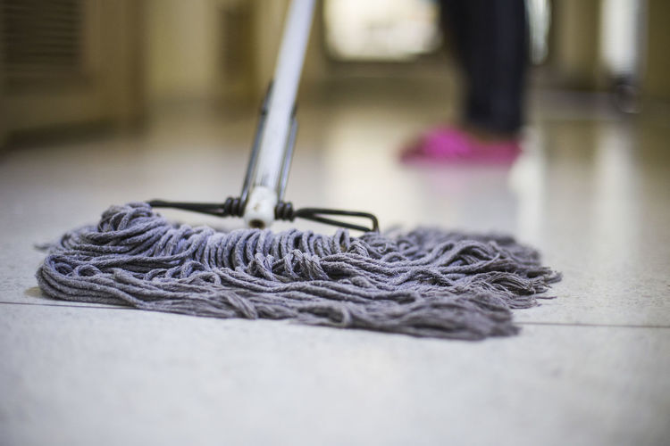Low section of person cleaning floor with mop