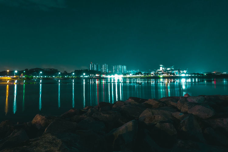 Illuminated rocks by sea against sky at night