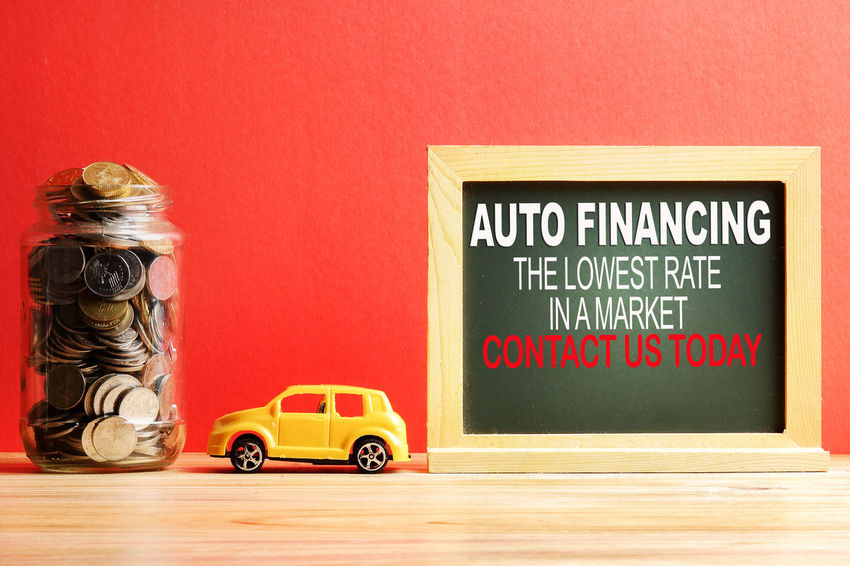 AUTO FINANCING: LOWEST RATE IN A MARKET CONCEPT with coins in the jar and miniature car. Western Script Text Communication Car No People Still Life Indoors  Toy Table Motor Vehicle Mode Of Transportation Toy Car Yellow Red Transportation Sign Small Auto Financing Loan  Interest Rate Lowest Contact Us