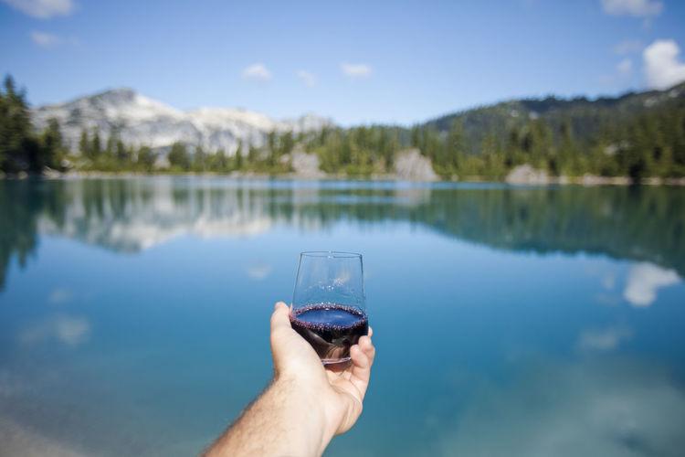 Man hand on lake against sky