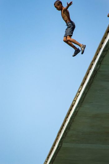 Low angle view of man jumping against clear blue sky