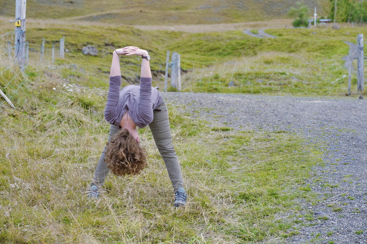 Rear view of woman doing yoga on a field