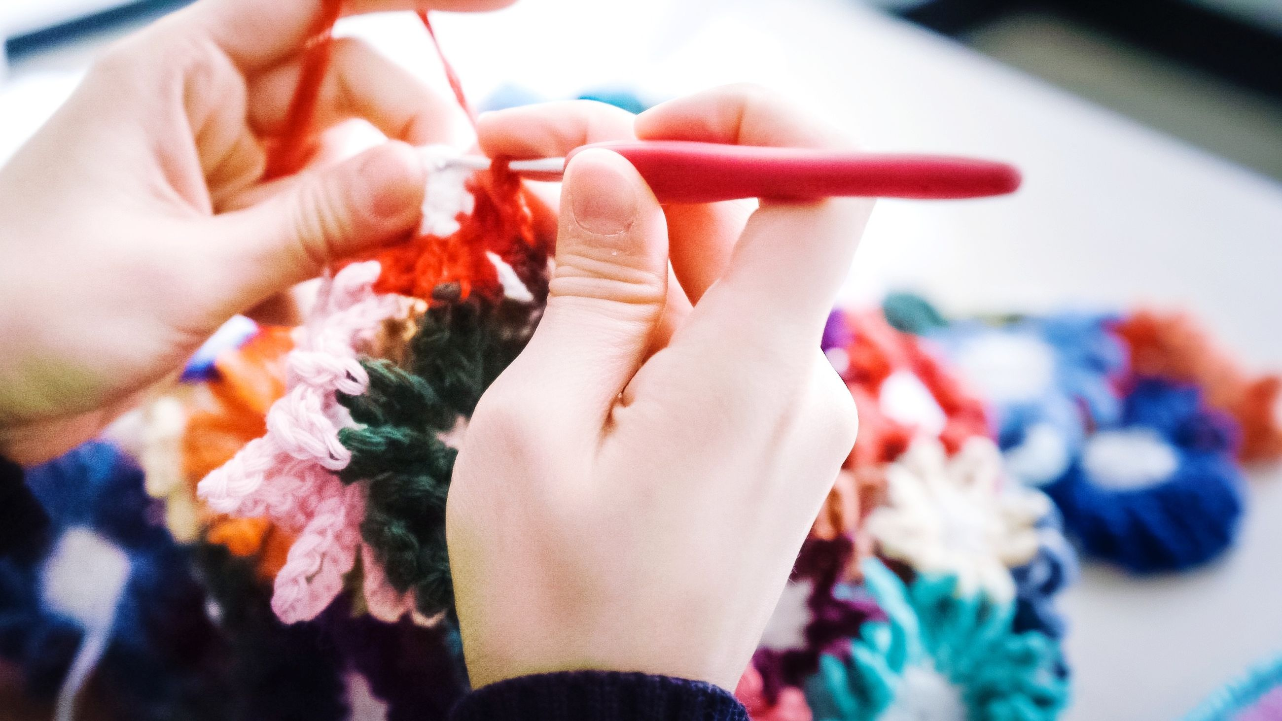 human hand, hand, human body part, wool, holding, real people, indoors, one person, art and craft, close-up, knitting, creativity, skill, selective focus, craft, body part, leisure activity, lifestyles, adult, finger, human limb