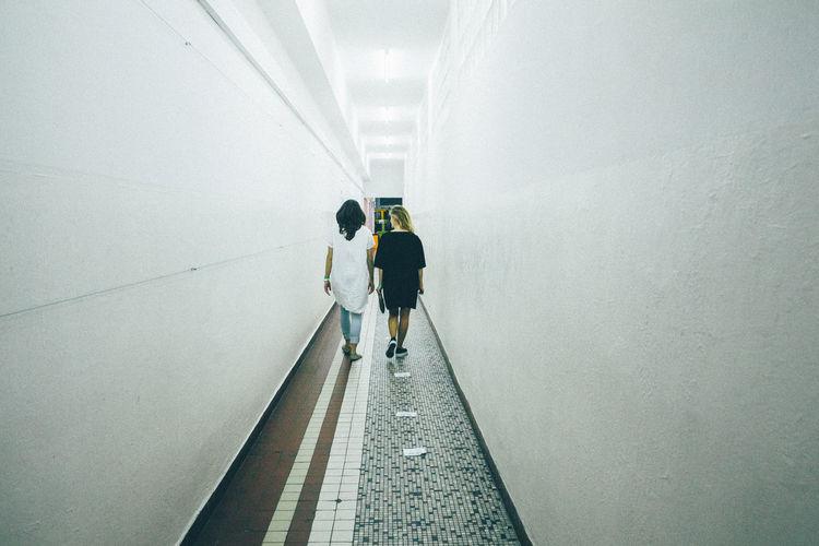 Rear view of friends walking in corridor