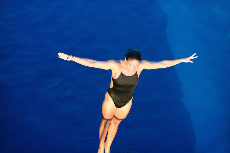 Female Diver On Platform, Preparing To Dive, View From Above Copy Space Swimming Diving Arms Athlete Horizontal Individual Sports Water Sport Woman Black Blue Blue Background Dive Female Muscular Build One Person Outdoors Pool Sport Strength Swimming Pool Water Water Surface Young Adult Young Women