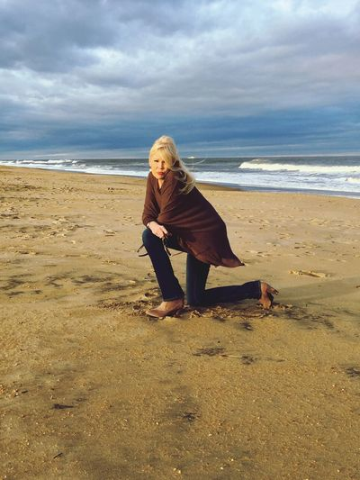 Full length of woman kneeling on sea shore at beach against cloudy sky