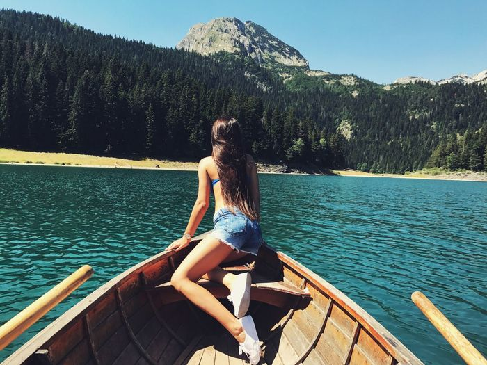 Young woman sitting on boat against lake