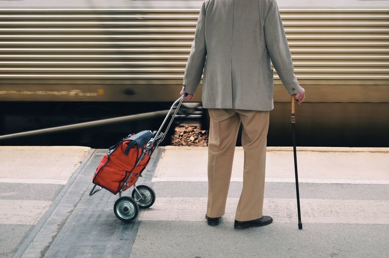 Low section of man with luggage standing at railroad station platform