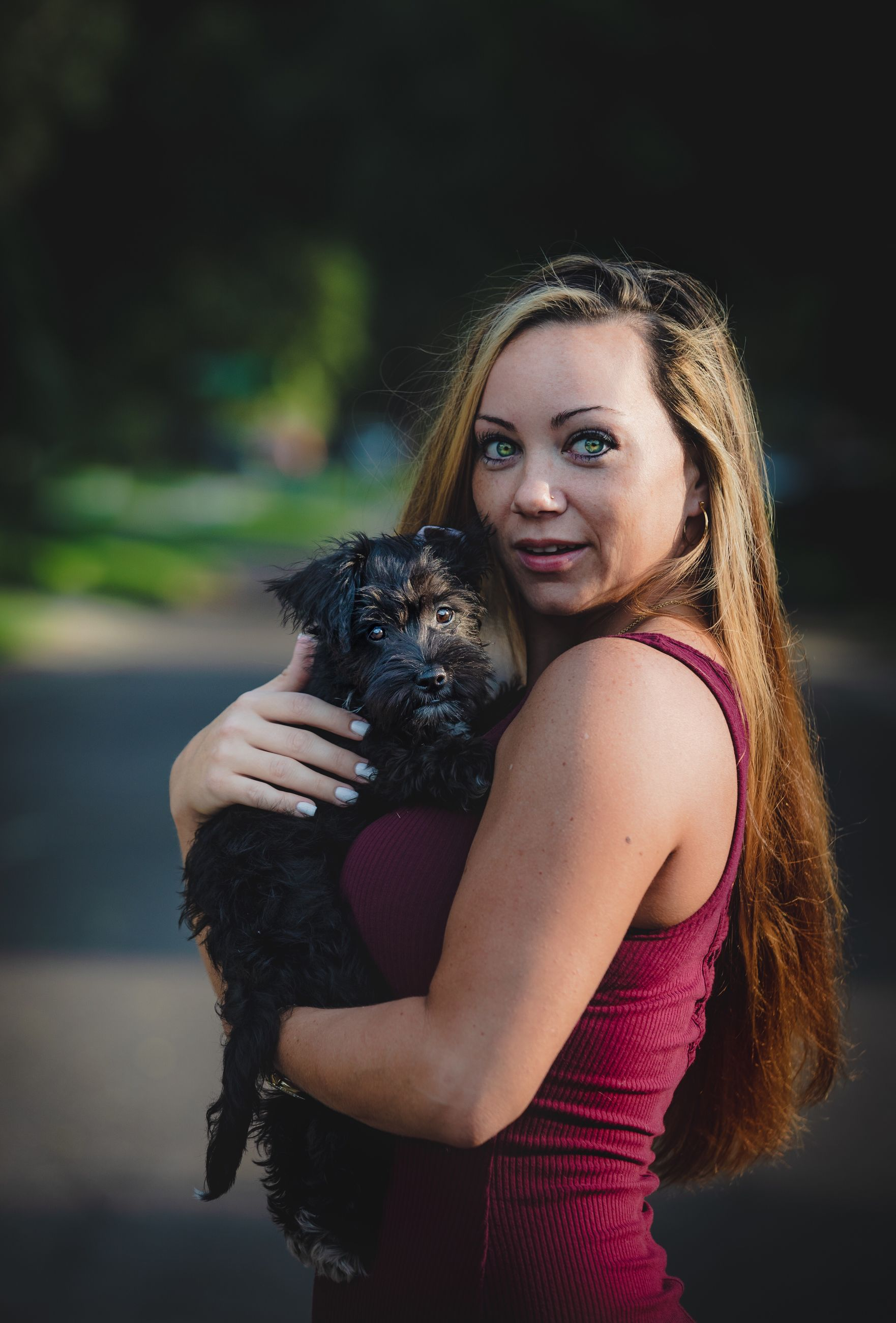 PORTRAIT OF YOUNG WOMAN WITH DOG ON RED