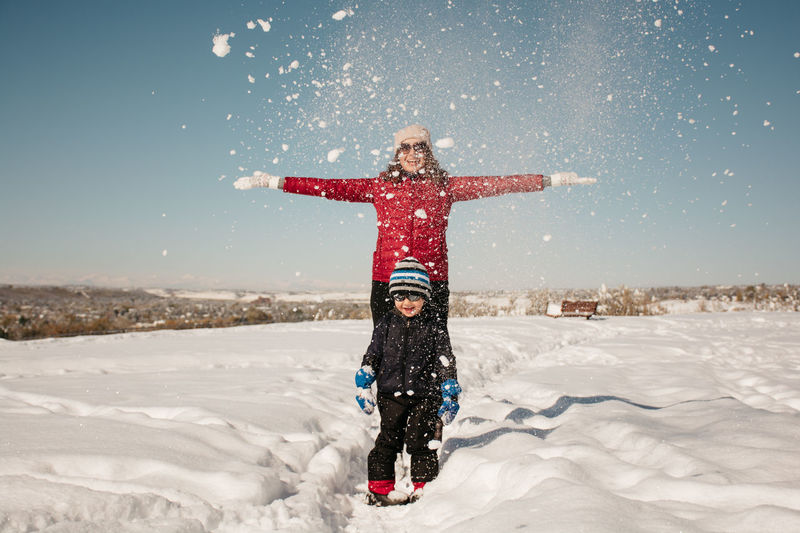Mother and son having fun in the snow Family Fun Arms Outstretched Boy Child Clothing Cold Temperature Happiness Leisure Activity Nature Outdoors Park Sky Snow Snowflakes Snowing Warm Clothing Winter Moments Of Happiness