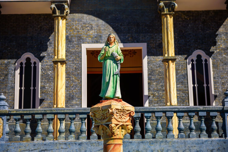 Statue of angel outside temple against building