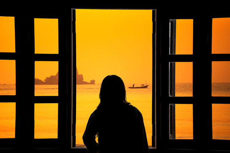 Rear view of silhouette woman looking through window at sunset
