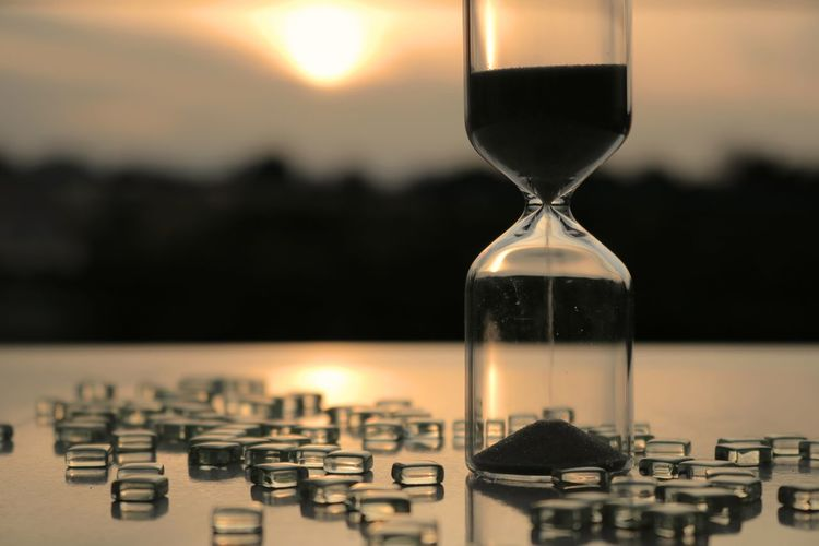 Close-Up Of Hourglass On Table During Sunset