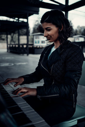 Side view of woman using piano
