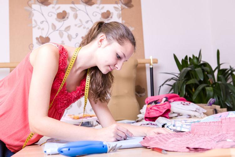 Female fashion designer working on fabric