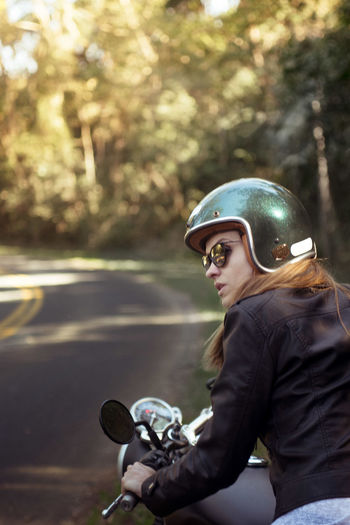 Young woman in jacket riding motorcycle on road