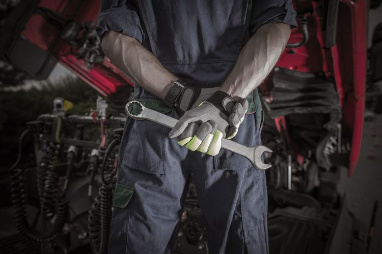 Semi Truck Pro Mechanic. Caucasian Service Worker with Heavy Duty Wrench Preparing For Complicated Truck Fix. Fix  Fixer Mechanic Worker Close-up Day Focus On Foreground Holding Human Body Part Human Hand Indoors  Men Midsection Occupation One Man Only People Professional Real People Semi Truck Standing Truck Trucking Weapon Working Wrench