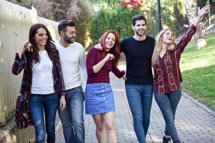 Group of students together outdoors in urban background. Women and men walking in the street wearing casual clothes. Adult Adults Only Casual Clothing Cheerful Day Friendship Front View Happiness Human Body Part Jeans Leisure Activity Lifestyles Looking At Camera Nature Outdoors People Portrait Smiling Standing Student Togetherness Tree University Student Young Adult Young Women