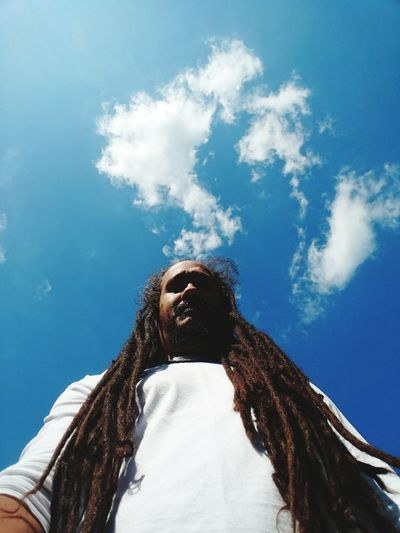 Low Angle View Of Man With Dreadlocks Against Blue Sky