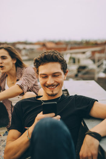 Portrait of a smiling young man using smart phone against sky