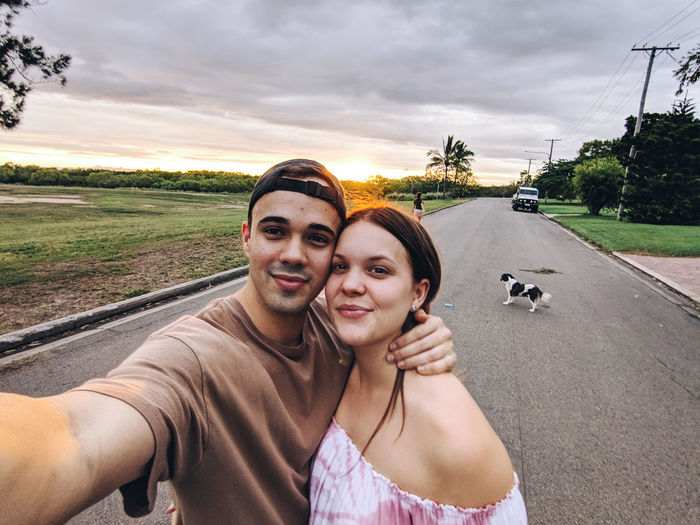 Portrait of smiling friends on road during sunset