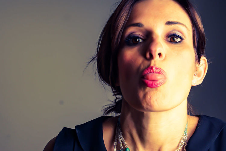Close-up portrait of beautiful woman sticking out tongue against gray background