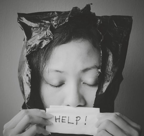 Close-Up Of Woman Holding Help Placard Against Black Background