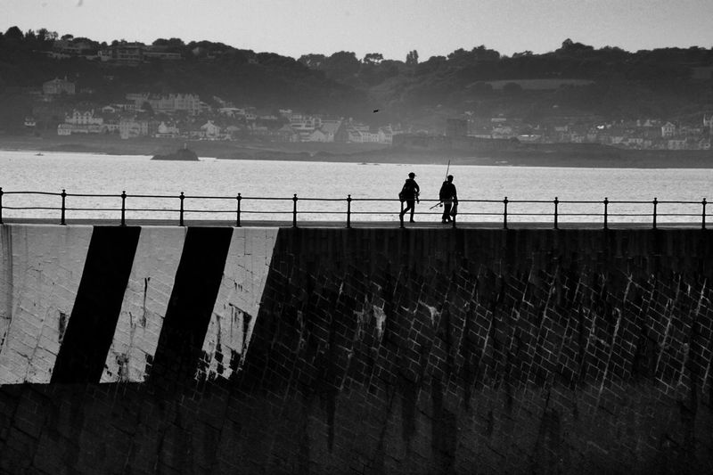 Low angle view of silhouette people walking on bridge