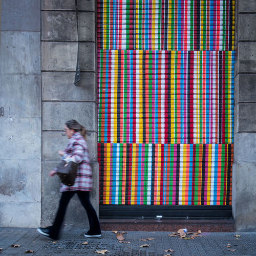 Side view of woman walking against colorful closed shutter