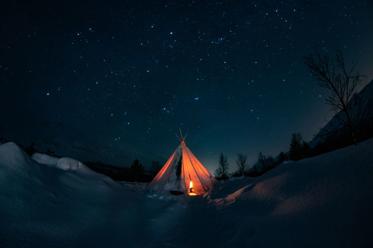 Tent on snow covered field against sky at night