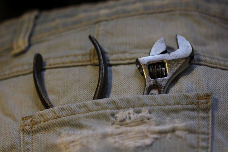Close-up of wrench and plier on person back pocket